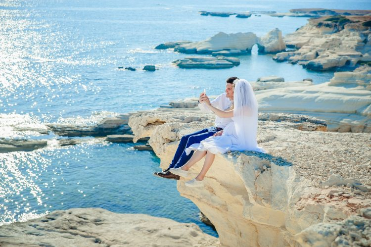 woman in wedding dress sitting beside man in costume on the stone facing the sea